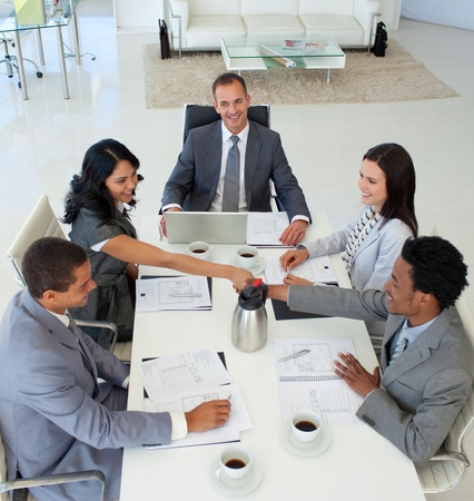 Businesswoman and businessman shaking hands in a meeting photo
