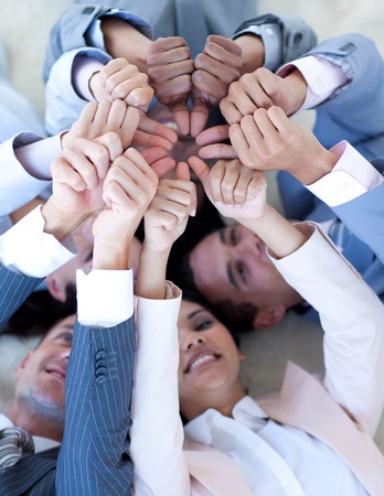 Business team on floor in a circle with thumbs up photo