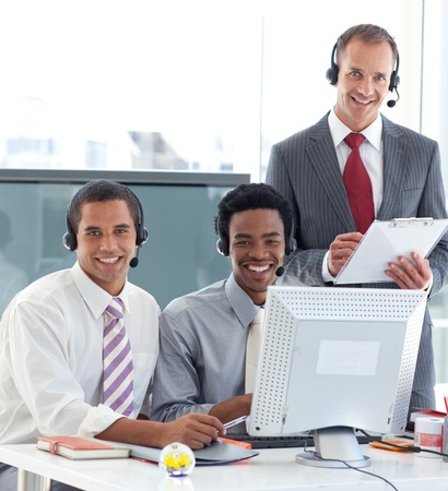 Manager talking to two businessmen in call center photo