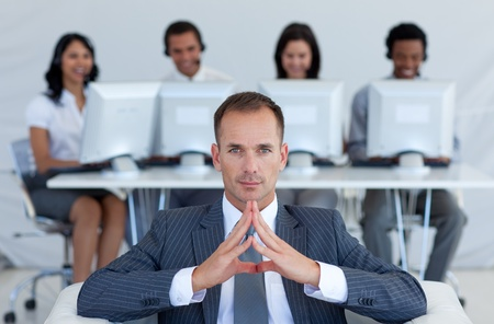 Manager sitting in call center in front of his team photo