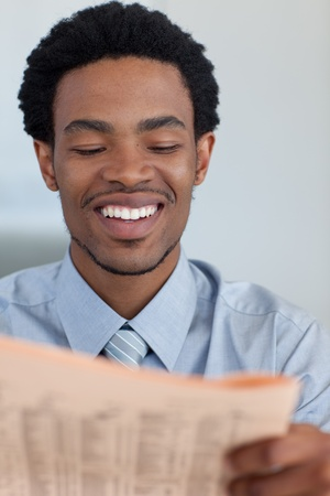 Smiling Afro-American businessman reading a newspaper photo