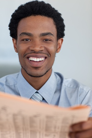 Afro-American businessman with a newspaper smiling at the camera photo