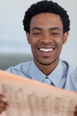 Attractive Afro-American businessman reading a newspaper photo