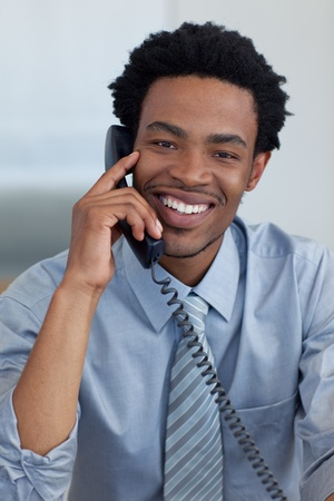 conference call: Portrait of smiling Afro-American businessman on phone in office