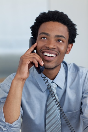Attractive smiling Afro-American businessman on phone in office photo