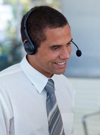 Businessman with a headset on in a call center photo