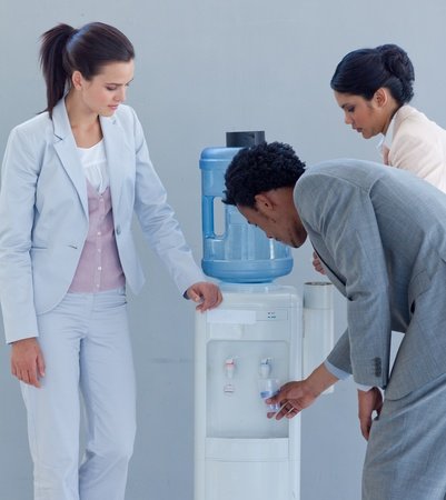 Business people drinking from a water cooler photo
