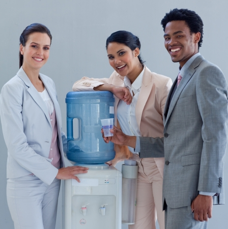 man drinking water: Smiling business people with a water cooler in office