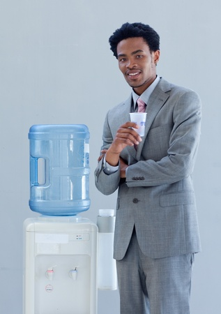 Businessman with a water cooler in office photo