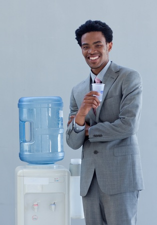 Businessman drinking from a water cooler in office photo