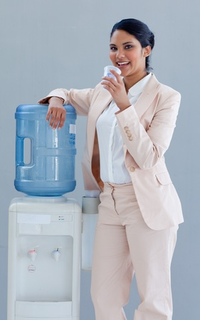 standing water: Businesswoman drinking from a water cooler Stock Photo