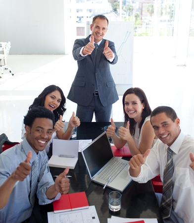 Business team in a meeting with thumbs up photo