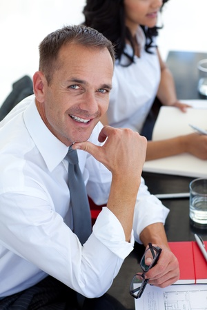 businessmeeting: Businessman in a meeting smiling at the camera
