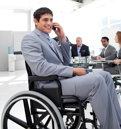 handicapped accessible: Businessman in a wheelchair on phone during a meeting Stock Photo