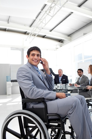 Smiling businessman on phone sitting in a wheelchair photo