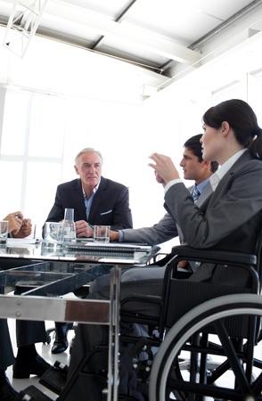 handicap: Imprenditrice attraente in una sedia a rotelle durante una riunione