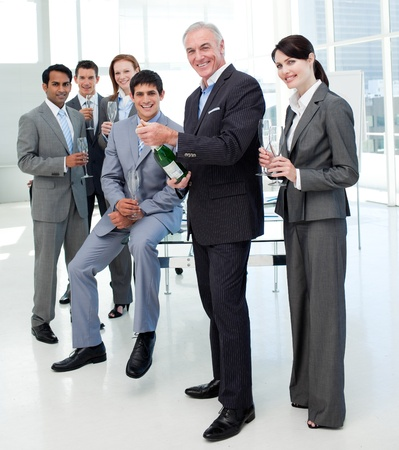 satisfied: Businessman opening a bottle of Champagne to celebrate a success Stock Photo