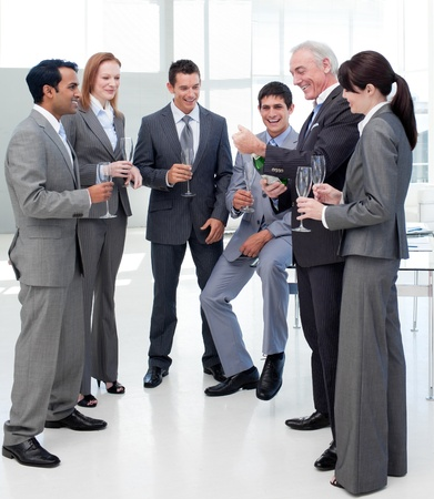 employee satisfaction: Senior manager opening a bottle of Champagne to celebrate a success with his team  Stock Photo