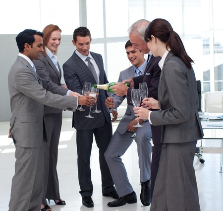 Successful businessman serving Champagne to his colleagues  photo