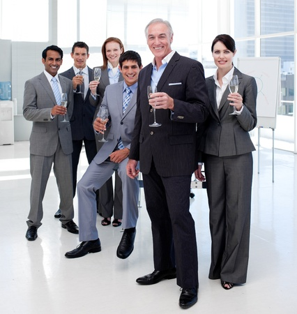 Multi-ethnic business people toasting with Champagne photo