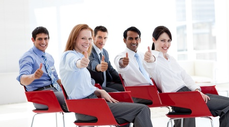 training consultant: Business people with thumbs up at a conference