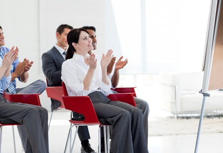 Multi-ethnic business people clapping at the end of a conference photo
