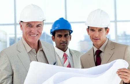 Smiling architects studying blueprints photo