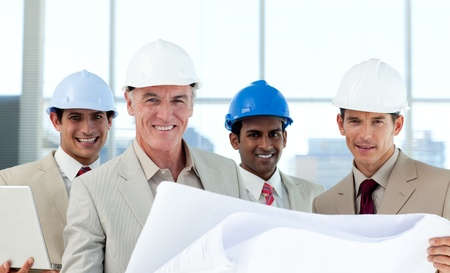 skills diversity: Smiling group of architect examining blueprints