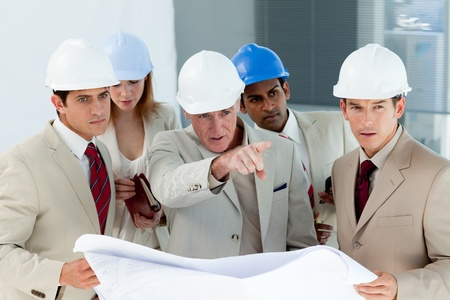 Serious architect looking at blueprints and pointing photo