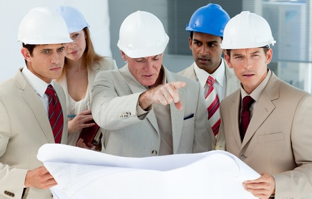 Multi-ethnic engineers studying plans  photo