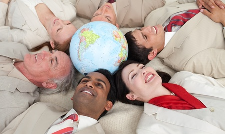 businessmeeting: Smiling business people lying around a globe Stock Photo