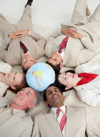 businessmeeting: International business people lying on the floor around a terrestrial globe