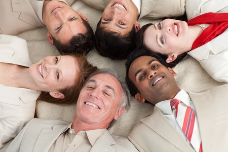 Business team lying on the floor with heads together Stock Photo - 10094883
