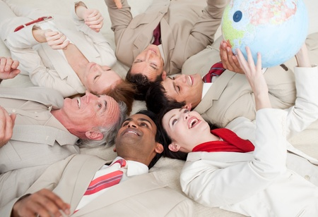 businessmeeting: Business team lying on the floor playing with a terrestrial globe