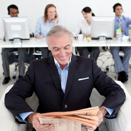 Smiling businessman reading a newspaper  photo