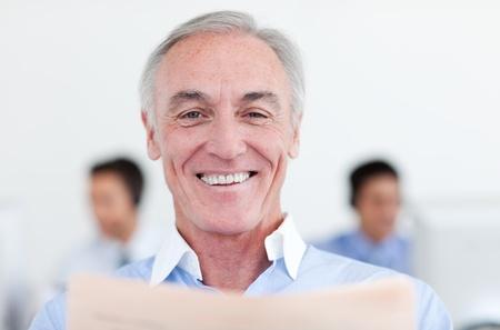Smiling senior businessman reading  photo