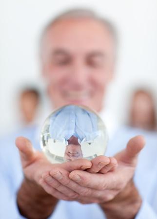bola de cristal: Empresario Senior sosteniendo una bola de cristal