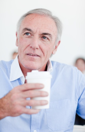 Senior businessman holding a drinking cup  photo