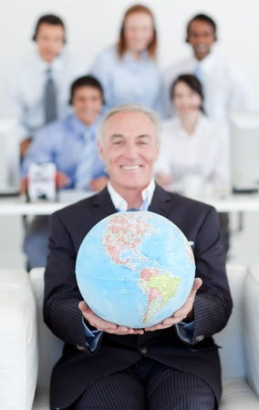 businessmeeting: Senior manager holding a terrestrial globe
