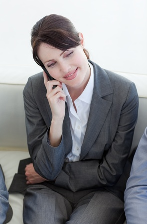 Smiling businesswoman on phone while waiting for a job interview photo