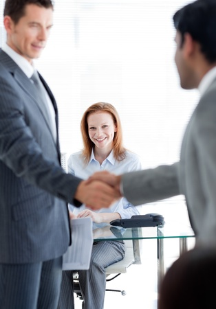 International businessmen greeting each other at a job interview  photo
