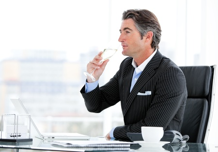 Charismatic businessman drinking a glass of water photo