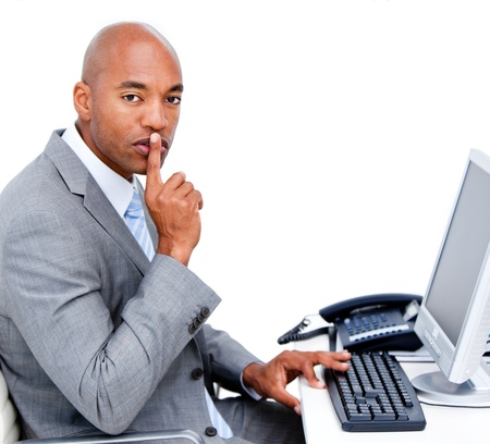 Confident businessman asking for silence sitting at his desk  photo