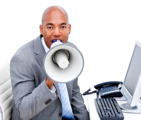 Furious businessman yelling through a megaphone sitting on his desk  photo