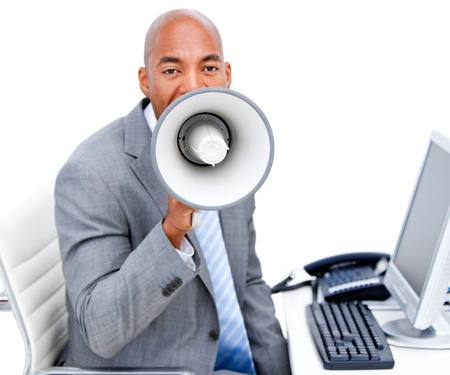 Furious young businessman yelling through a megaphone sitting on his desk  photo