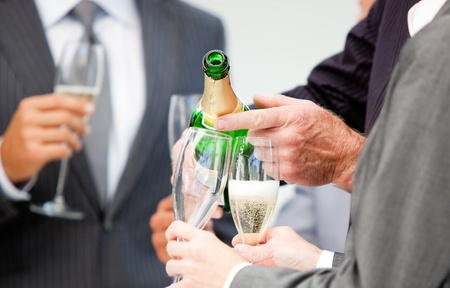 Close-up of a businessman serving Champagne  photo