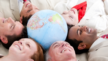Multi-ethnic business people lying around a globe photo