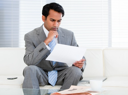 Confident businessman reading a note Stock Photo - 10078112