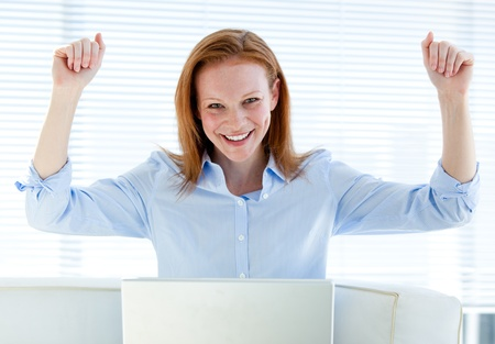 positive thinking: Bright business woman punching the air