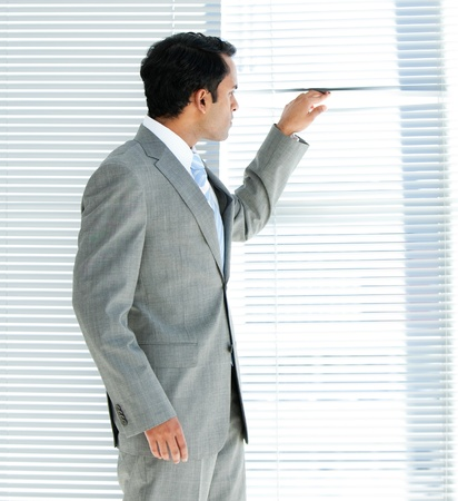 looking out: Confident businessman looking through a window Stock Photo